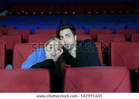 Young man and woman watch movie and press close to one another in fright in cinema theater.