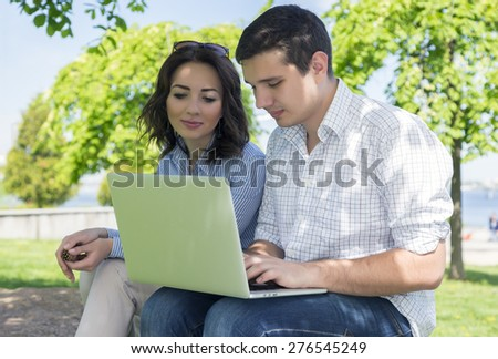 Young man and woman with flowers. Young cute male and female two people sitting in park with laptop computer casual dress code working together
