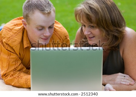 young man and woman with laptop outdoor