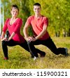 Young man and woman woman doing yoga in the sunny summer park - stock photo