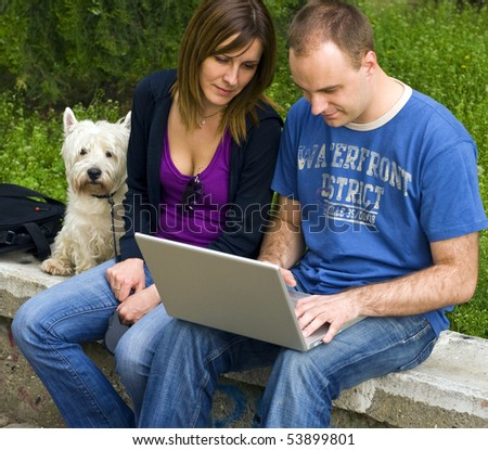 Young man and woman working on the lap top - stock photo