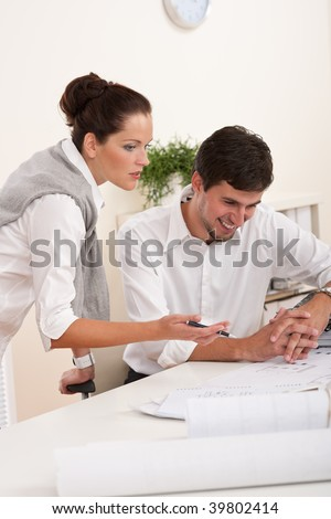 Young man and woman working together at the office