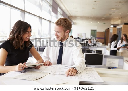 Young man and woman working together in architect?s office - stock photo