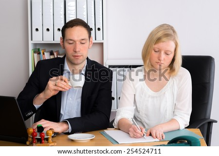 young man and woman working together in the office
