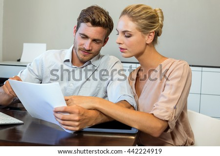 Young man and woman working while sitting in office - stock photo