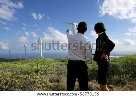 Young man and young woman in suit face to a wind turbine - stock photo