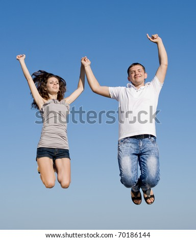Young man and young woman jumping on background of sky