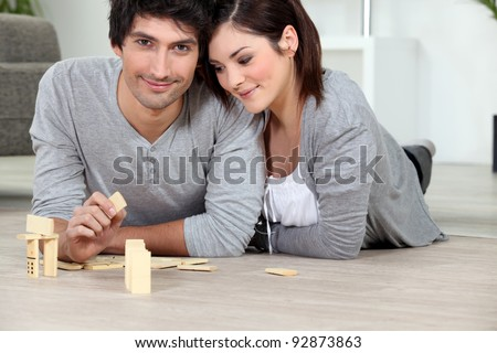 Young man and young woman playing dominoes