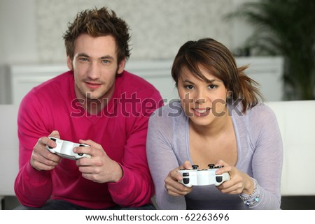 Young man and young woman playing video game - stock photo