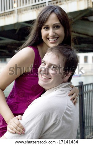 Young man and young woman posing with her arm on his shoulder being lifted in the air by him - stock photo