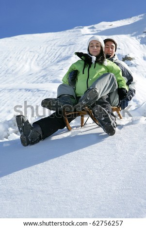 Young man and young woman sledding in snow - stock photo