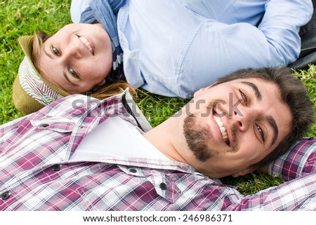 Young man and young woman smiling in park - stock photo