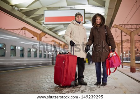 Young man and young woman stand with big red roll-on bag on railway platform holding hands