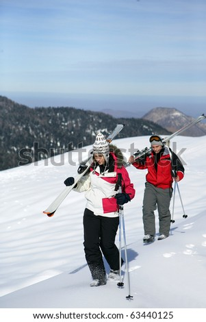 Young man and young woman walking in snow - stock photo