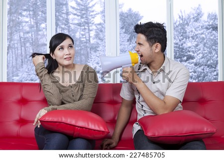 Young man angry to his girlfriend and shouting with megaphone in winter day - stock photo