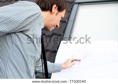 young man architect presenting a project against the background of the roof and windows - stock photo