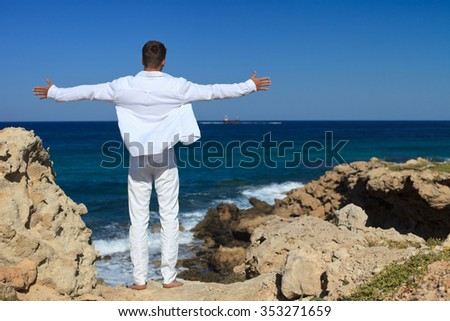young man arms outstretched, standing on a rock by the sea. horizontal angle  - stock photo