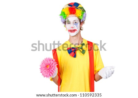 Young man as a clown holding a flower - stock photo