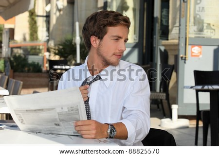 Young man at a cafe table reading a newspaper - stock photo