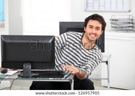 Young man at a computer - stock photo