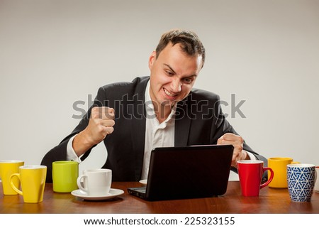 young man at a computer full of dirty cups - stock photo