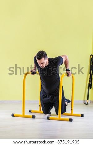 Young man at gym, exercising push ups with handles - stock photo