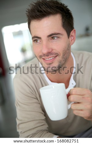 Young man at home drinking coffee - stock photo
