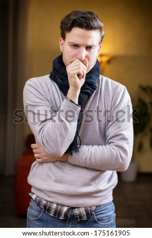 Young man at home sick, coughing, with hand in front of his mouth - stock photo