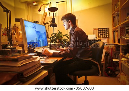 Young man at home using a computer - stock photo
