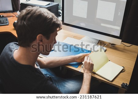 Young man at home using a computer, freelance developer or designer working at home - stock photo