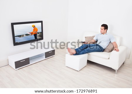 Young Man At Home Watching News On Television - stock photo