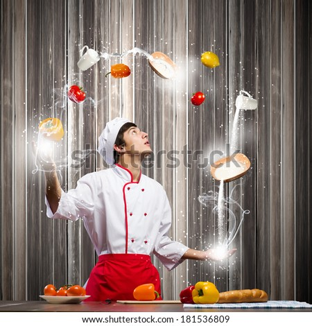 Young man at kitchen juggling with ingredients - stock photo