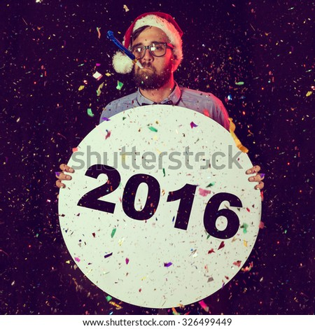 Young man at New Year's Eve party, having fun, wearing Santa's hat, holding cardboard circle and blowing party whistle - stock photo