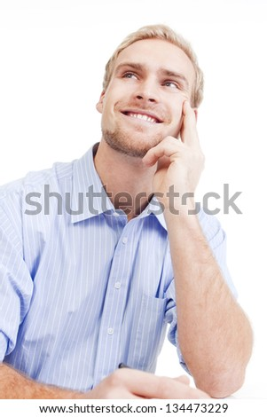 young man at office, sitting, daydreaming, smiling