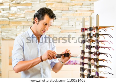 Young man at optician with glasses, he might be customer or salesperson and is looking for sunglasses - stock photo