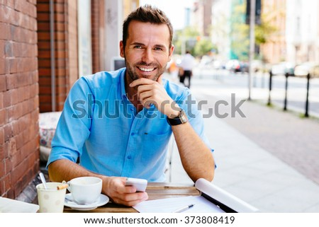 Young man at outdoors cafe smiling - stock photo