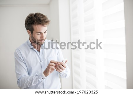 young man at phone typing an sms