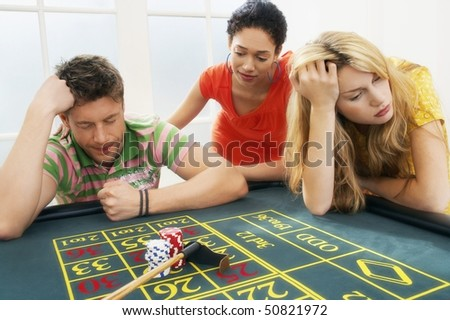 Young man at roulette table losing large bet - stock photo