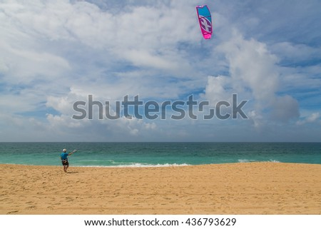 Young man at the beach with a kite learning how to control the kite in the wind
