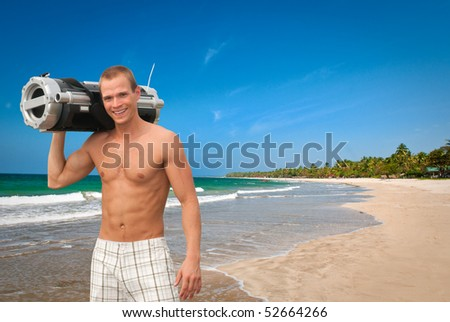 Young man at the beach with a music player on the shoulder - stock photo