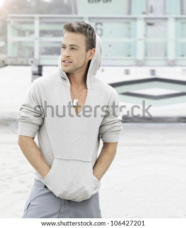 Young man at the beach with hands in pockets - stock photo