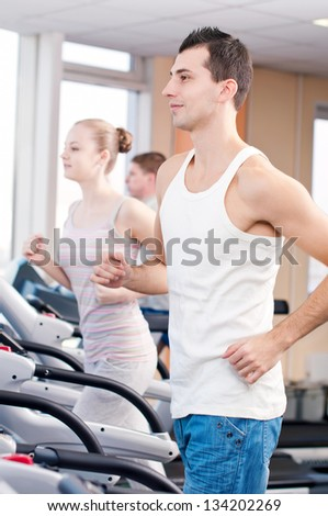Young man at the gym exercising. Run on on a machine.