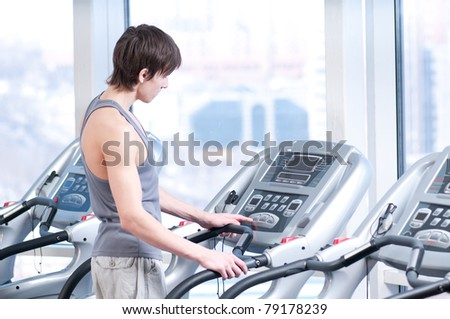 Young man at the gym exercising. Run on on a machine. - stock photo