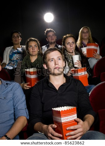 Young man at the movie theater with bag of popcorn - stock photo