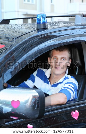 Young man at wheel of black wet  offroader with stickers hearts and blue flasher. Pink wedding. - stock photo