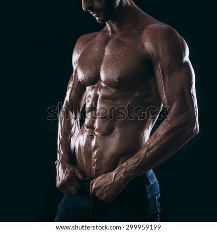 young man athlete bodybuilder torso on black background - stock photo