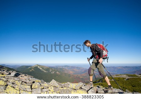 Young man backpacker walking on the rocky ridge of the mountain with beautiful high altitude landscape view on the background. Hiker using trekking sticks. Fall. - stock photo