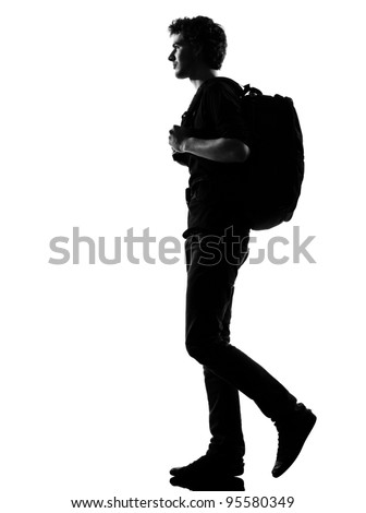 young man backpacker walking silhouette in studio isolated on white background