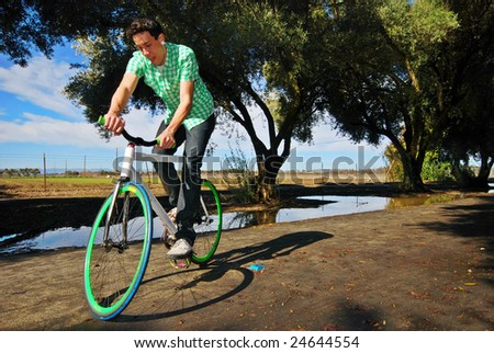 Young man balancing on his fixed gear bicycle