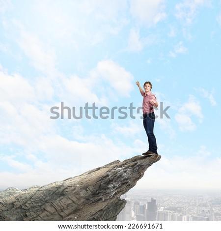 Young man balancing on one leg on edge of rock - stock photo